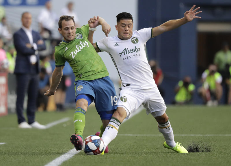 Seattle Sounders midfielder Harry Shipp, left, is challenged by Portland Timbers defender Jorge Moreira, right, during the first half of an MLS soccer match, Sunday, July 21, 2019, in Seattle. (AP Photo/Ted S. Warren)