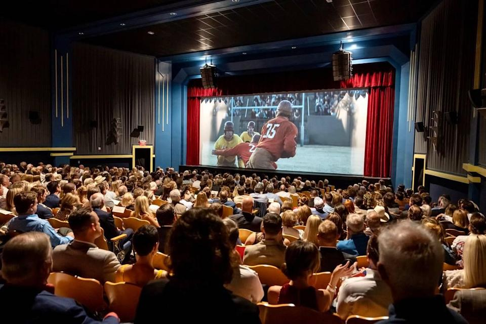 """A VIP crowd watches the """"12 Mighty Orphans"""" premiere June 7, 2021, in the restored New Isis theater in the Stockyards. (For a few moments, the house lights weren't dimmed.)"""
