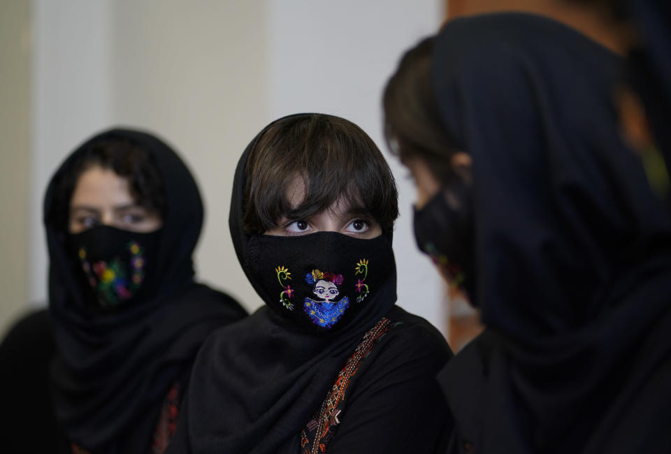 Fatemah, center, a member of the Afghan all-girls robotics team, speaks during an interview in Mexico City, Wednesday, Aug. 25, 2021. After international efforts and coordination from a diverse group of volunteers to evacuate the team, the girls are begging the international community to help get their families to safety amid evacuations for people fleeing the Taliban takeover as the U.S. pulls out. (AP Photo/Eduardo Verdugo)