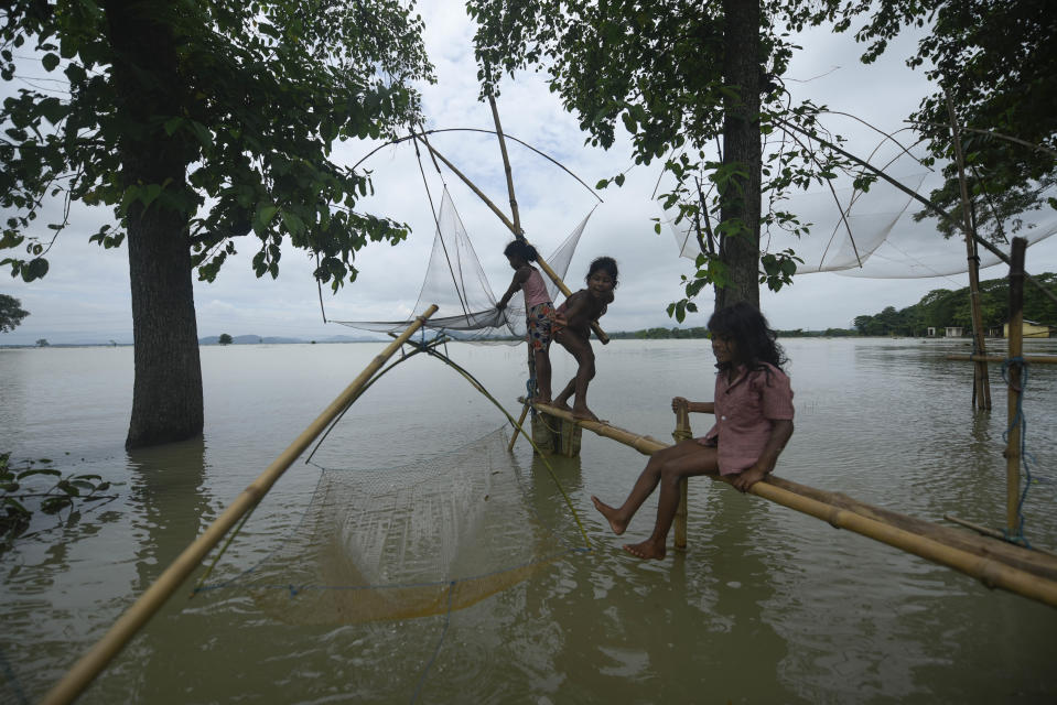 Children fishing in a flooded area in a flood effected village in Morigaon district of Assam in India on Friday, 17 July 2020. (Photo by David Talukdar/NurPhoto via Getty Images)