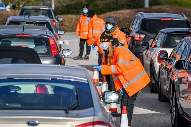 Testing staff hand out kits to motorists attending a surge testing centre