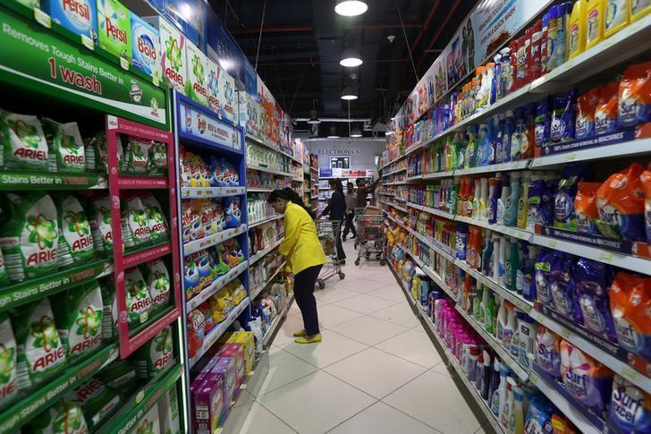 Employees check stock at the Alpha Supermarket under which Tesco products will be stocked in Karachi,