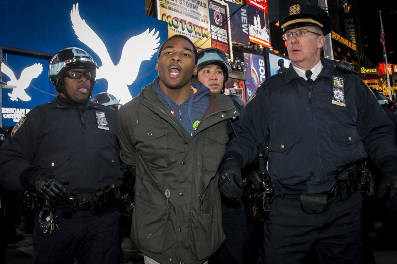 New York City Police NYPD officers detain a demonstrator protesting against the verdict announced in the shooting death of Michael Brown, as they block traffic in Times Square, New York