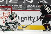 Minnesota Wild goaltender Cam Talbot (33) makes a save on a shot from Arizona Coyotes left wing Johan Larsson (22) during the second period of an NHL hockey game Wednesday, April 21, 2021, in Glendale, Ariz. (AP Photo/Ross D. Franklin)