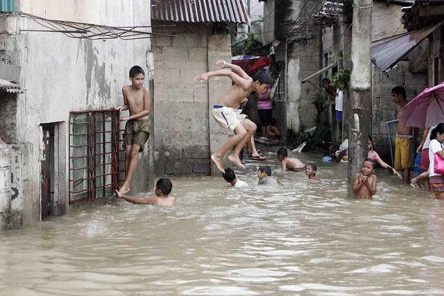 "Children play in the flooded village of Barangay Malanday in low-lying Marikina City, northeast of Manila, despite rising floodwaters from continuous rains brought on by Typhoon 'Gener'. Marikina City officials have started preparing to forcibly evacuate residents from some high-risk areas after the water level at the Marikina River rose to 16 meters early today, raising the alert level at the river to ""2."" (Mike Alquinto/NPPA Images)"