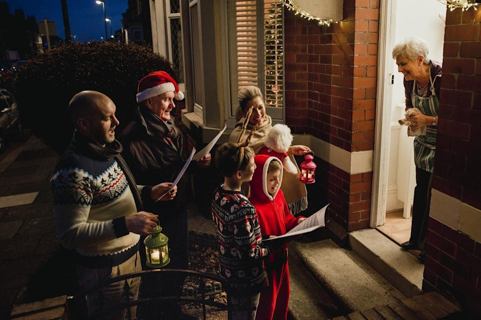 Parents, children, and grandfather singing carols for senior woman