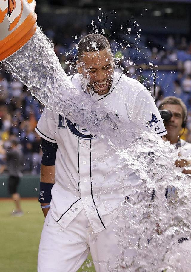 Tampa Bay Rays' James Loney gets doused with ice water by teammate Yunel Escobar after hitting a ninth-inning, game-winning home run off Baltimore Orioles relief pitcher Tommy Hunter during a baseball game Monday, Sept. 23, 2013, in St. Petersburg, Fla. The Rays won the game 5-4. (AP Photo/Chris O'Meara)