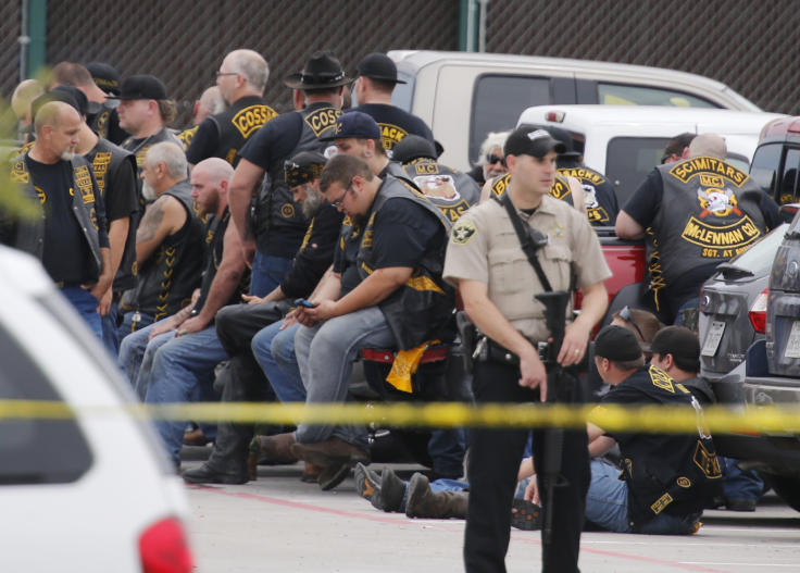 A McLennan County deputy stands guard near a group of bikers in the parking lot of Twin Peaks restaurant in Waco, Texas, last month. (Rod Aydelotte/Waco Tribune-Herald via AP)