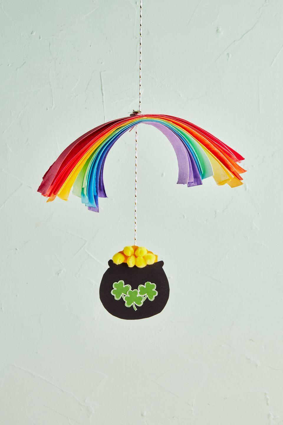 """<p>Gold, or mini yellow pom-poms? Either way, craft this DIY hanging mobile and lots of luck and riches will surely come your way!</p><p><strong>To make:</strong> Cut 1-inch-wide strips of paper from colored craft paper. Use a hole-punch to make a hole in the middle of each strip of paper; stack paper in the order of the rainbow. Thread a piece of twine through holes, knotting it just above and below the paper to hold paper in place. Fold a piece of black craft paper in half and cut out a pot shape, so that you have two identical pieces. Cut out two dome-shaped pieces of yellow craft paper and sandwich between the black pieces, gluing everything together. Glue mini yellow pom-poms to the yellow paper. Punch a hole at the top of the yellow dome, and thread twine through, securing with a knot. Cut out mini clovers from green craft paper and glue to the front and back of the pot; outline with a white pen if desired.<br><br><a class=""""link rapid-noclick-resp"""" href=""""https://www.amazon.com/Sheets-Origami-Colors-Stationery-Perfect/dp/B07P53JWP6/ref=sr_1_1?tag=syn-yahoo-20&ascsubtag=%5Bartid%7C10050.g.4036%5Bsrc%7Cyahoo-us"""" rel=""""nofollow noopener"""" target=""""_blank"""" data-ylk=""""slk:SHOP PAPER"""">SHOP PAPER</a><br></p>"""