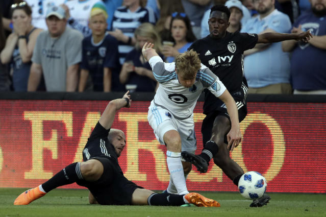Minnesota United midfielder Rasmus Schuller (20) tries to split Sporting Kansas City midfielder Yohan Croizet (10) and forward Gerso (12) during the first half of an MLS soccer match in Kansas City, Kan., Sunday, June 3, 2018. (AP Photo/Orlin Wagner)