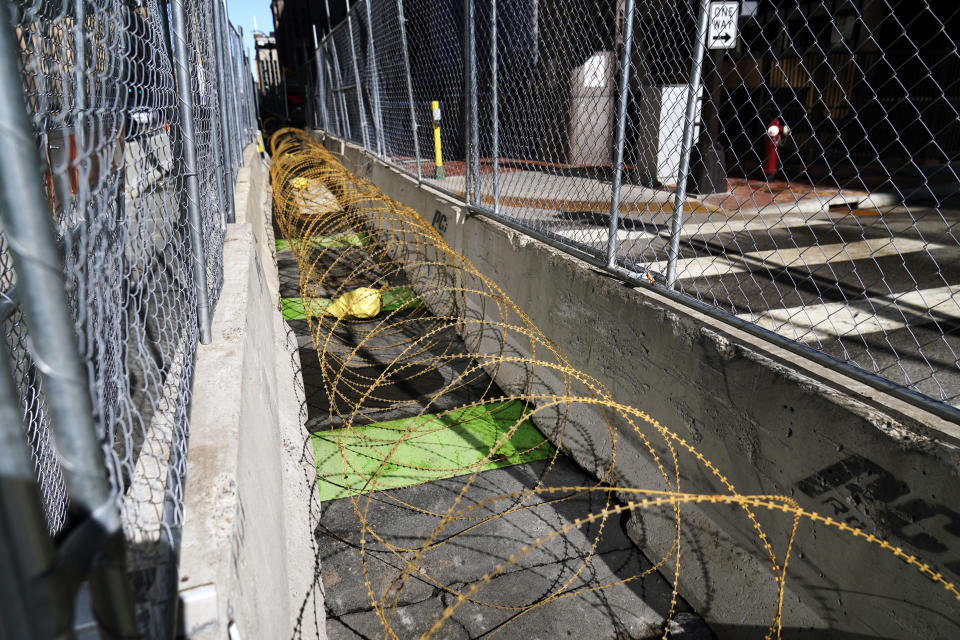 Concertina wire sits between fenced barriers outside the Hennepin County Government Center, Wednesday, Feb. 23, 2021, in Minneapolis, as part of security in preparation for the trial of former Minneapolis police officer Derek Chauvin. The trial is slated begin with jury selection on March 8. Chauvin is charged with murder the death of George Floyd during an arrest last May in Minneapolis. (AP Photo/Jim Mone)