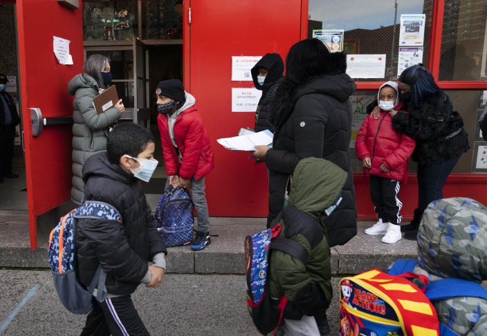 Students enter P.S. 134 Henrietta Szold Elementary School, Monday, Dec. 7, 2020, in New York. Public schools reopened for in-school learning Monday after being closed since mid-November. (AP Photo/Mark Lennihan)