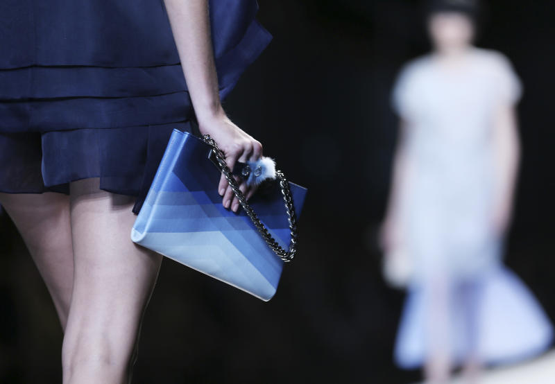 FILE - This Sept. 19, 2013 file photo shows a model holding a purse as she models a creation for the Fendi women's Spring-Summer 2014 collection during Milan Fashion Week in Milan, Italy. After weeks of top designer runway previews of spring styles at marathon fashion weeks in New York, London, Milan and Paris, the eye started to wander and it caught the newest trends for handbags and shoes. For some shoppers, accessories are at the forefront of the catwalk news they're waiting for. (AP Photo/Antonio Calanni, File)