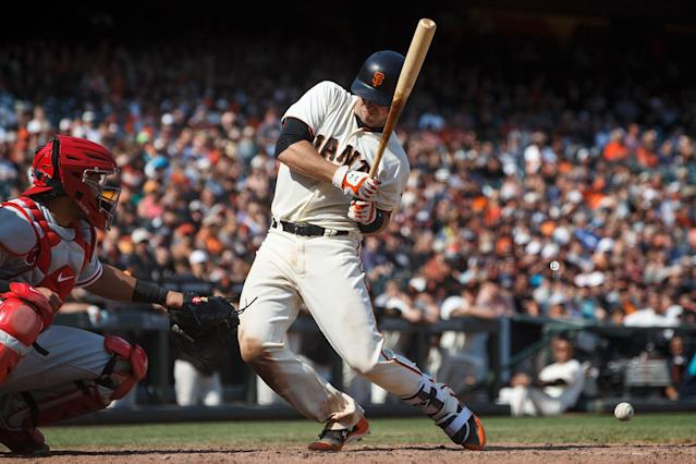 Buster Posey reacts after getting hit by a Hector Neris pitch. (Getty Images)