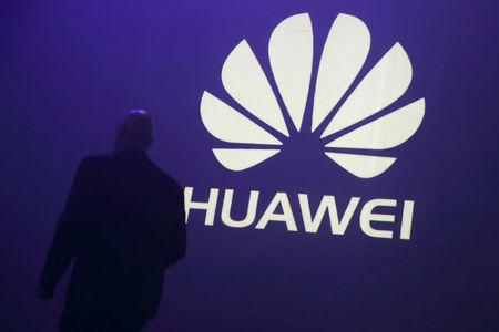 FILE PHOTO - A man walks past a logo during the presentation the Huawei's new smartphone, the Ascend P7, launched by China's Huawei Technologies in Paris