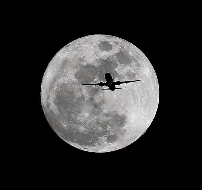 A commercial airliner crosses the first full Moon of the year, called the Wolf Moon over Whittier, Calif. on its way to Los Angeles Airport.