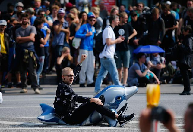 <p>A protester sits on an inflatable toy during a demonstration at the G20 summit in Hamburg, Germany, July 7, 2017. (Photo: Hannibal Hanschke/Reuters) </p>