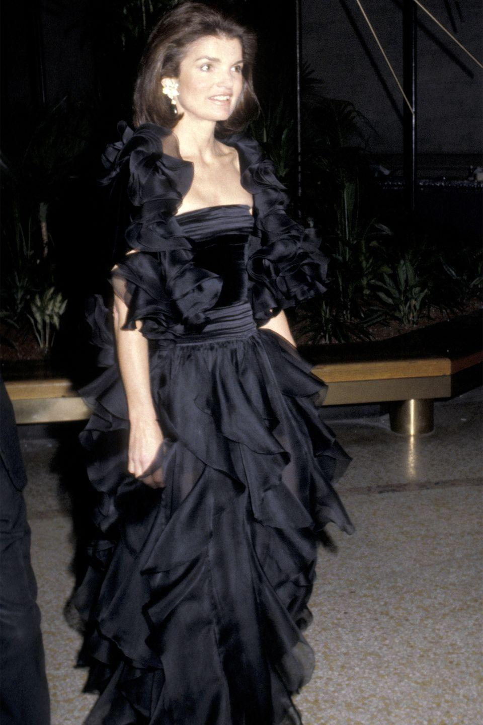 <p>Jackie epitomized late '70s glam with a ruffled black gown and big diamond earrings. </p>