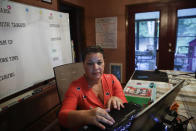 Aimee Rodriguez Webb works on her computer reading emails at her dinning room table that she set up as a virtual classroom for a Cobb County school, on Tuesday, July 28, 2020, in Marietta, Ga. After a rocky transition to distance learning last spring, Webb is determined to do better this fall. She bought a dry-erase board and a special camera to display worksheets, and she set up her dining room to broadcast school lessons. (AP Photo/Brynn Anderson)