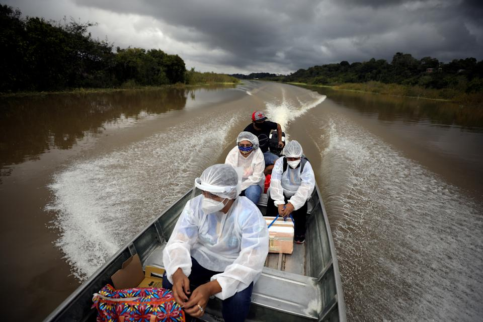Municipal health workers travel on a boat along the Solimoes river banks, where Ribeirinhos (river dwellers) live, to administer the AstraZeneca/Oxford vaccine for the coronavirus disease (COVID-19) to the residents, in Manacapuru, Amazonas state, Brazil, February 1, 2021. Picture taken February 1, 2021. REUTERS/Bruno Kelly     TPX IMAGES OF THE DAY