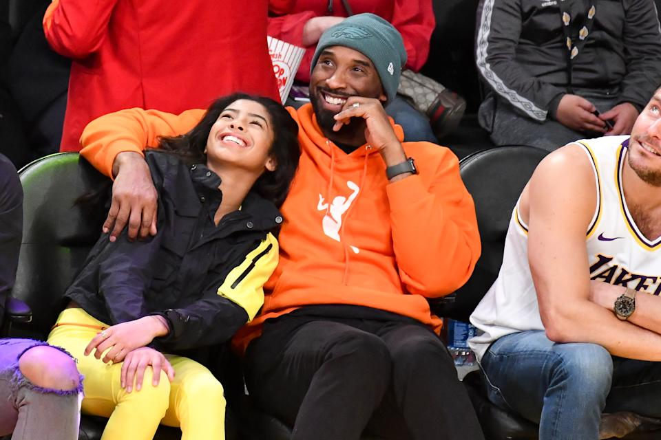 Kobe Bryant and daughter Gianna Bryant attend a basketball game.