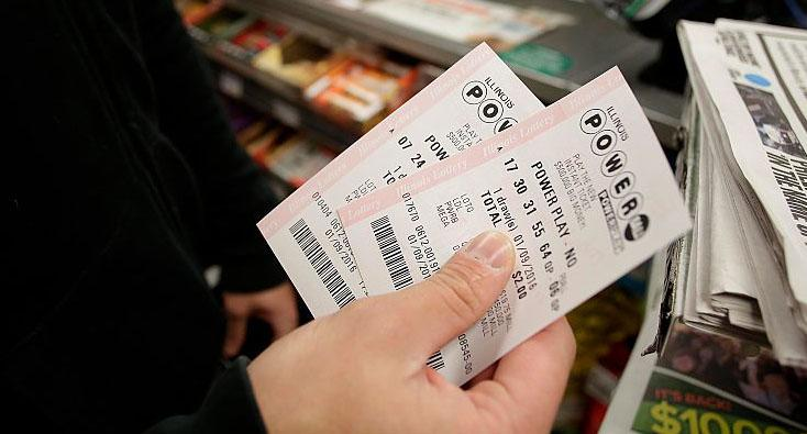 A file image of a man holding two Powerball tickets in his hand at a store.