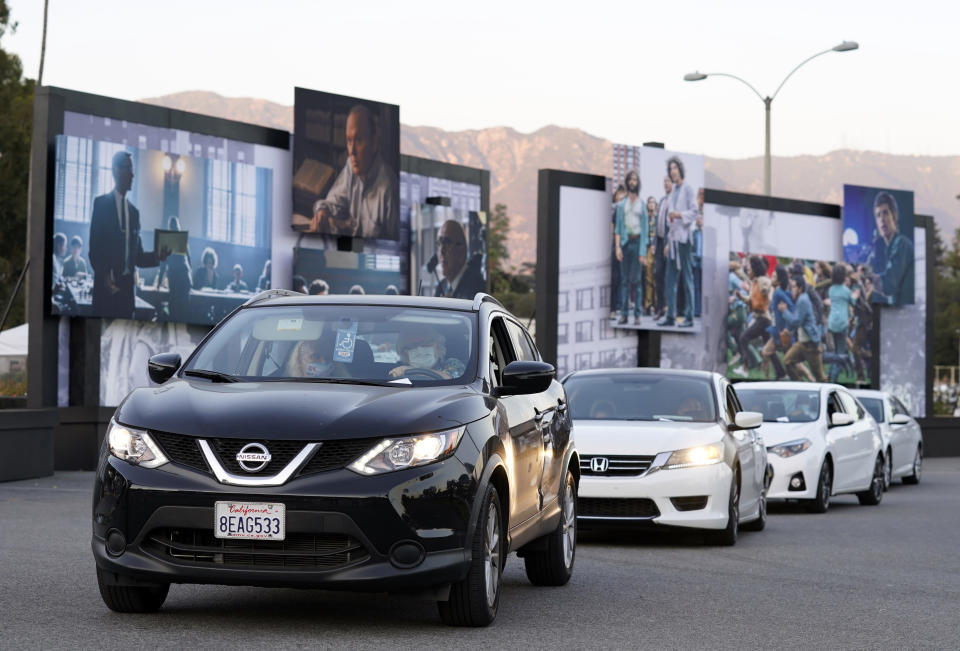 """FILE - Audience members in their cars drive past still photos from the Netflix film """"The Trial of the Chicago 7"""" at its drive-in premiere in Pasadena, Calif. on Oct. 13, 2020. Playing not just movies but concerts, graduations and church services, the drive-in was reborn as the pandemic's unlikely ark. (AP Photo/Chris Pizzello, File)"""