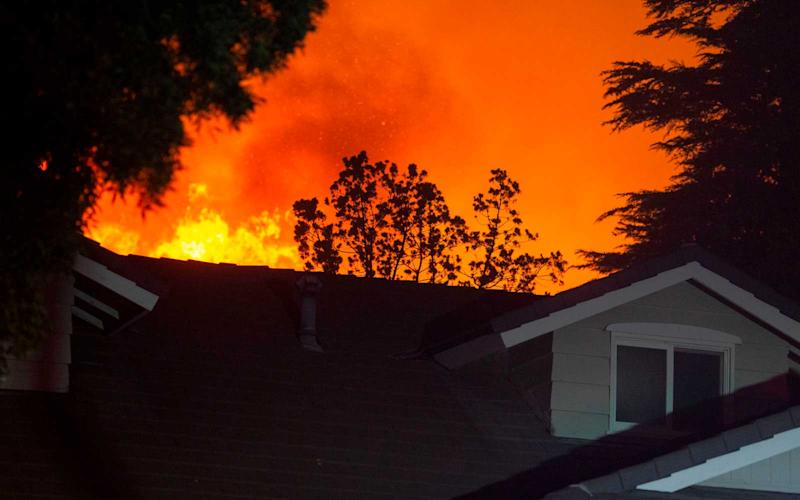 Flames from the Saddleridge Fire approach a home in the Porter Ranch section of Los Angeles, California, in the early morning hours of October 11, 2019. | DAVID MCNEW/Getty Images