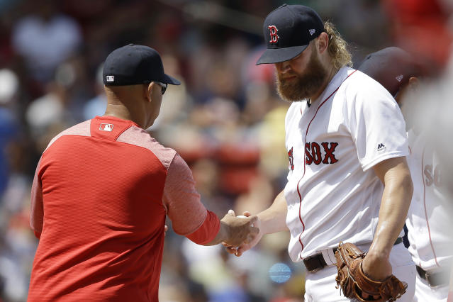 Boston Red Sox's Andrew Cashner, right, hands the ball to manager Alex Cora, left, as he is retired from a baseball game in the second inning against the Los Angeles Angels at Fenway Park, Sunday, Aug. 11, 2019, in Boston. (AP Photo/Steven Senne)