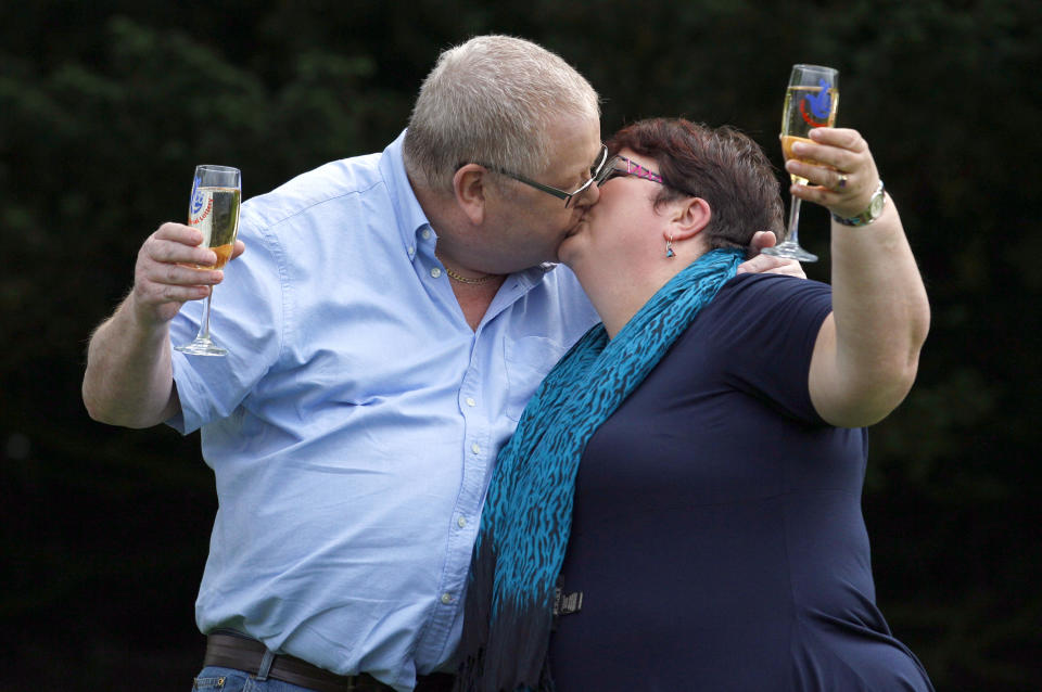 Colin Weir (L) and his wife Chris kiss they hold glasses of champagne after a news conference at a hotel near Falkirk, Scotland July 15, 2011. The couple scooped 161 million pounds ($259 million) in Tuesday's Euromillions jackpot.   REUTERS/David Moir (BRITAIN - Tags: SOCIETY)