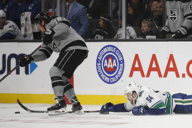 Vancouver Canucks' Tyler Motte, right, reaches for the puck against Los Angeles Kings' Tyler Toffoli during the second period of an NHL hockey game Saturday, Nov. 24, 2018, in Los Angeles. (AP Photo/Jae C. Hong)