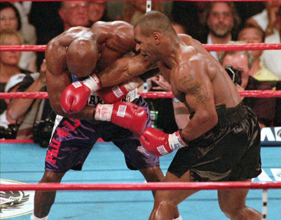 <p>Mike Tyson, right, lands a right to the face of WBA heavyweight champion Evander Holyfield during the third round, Saturday night, June 28, 1997, at the MGM Grand Garden in Las Vegas. Tyson was leading in the round until he lost two points for biting Holyfield's ear and pushing him. He was later disqualified in the round after biting Holyfield's other ear. (AP Photo/Lennox McLendon) </p>