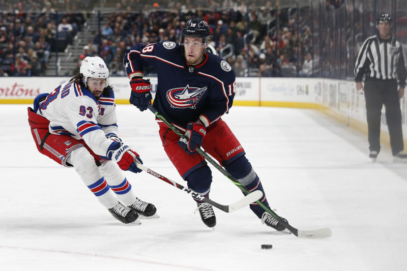 Columbus Blue Jackets' Pierre-Luc Dubois, right, looks for an open pass as New York Rangers' Mika Zibanejad, of Sweden, defends during the second period of an NHL hockey game Friday, Feb. 14, 2020, in Columbus, Ohio. (AP Photo/Jay LaPrete)