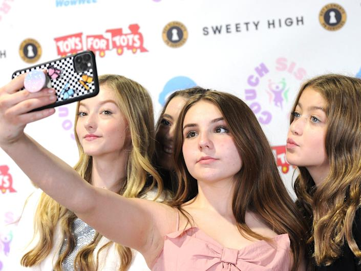 piper rockelle, center, holding her phone up at an angle to take a selfie of her and several other friends at a toys for tots event
