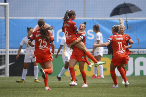 Houston Dash's Shea Groom (6) jumps in the arms of teammate Haley Hanson after scoring against the Utah Royals FC during the second half of an NWSL Challenge Cup soccer match at Zions Bank Stadium Tuesday, June 30, 2020, in Herriman, Utah. (AP Photo/Rick Bowmer)