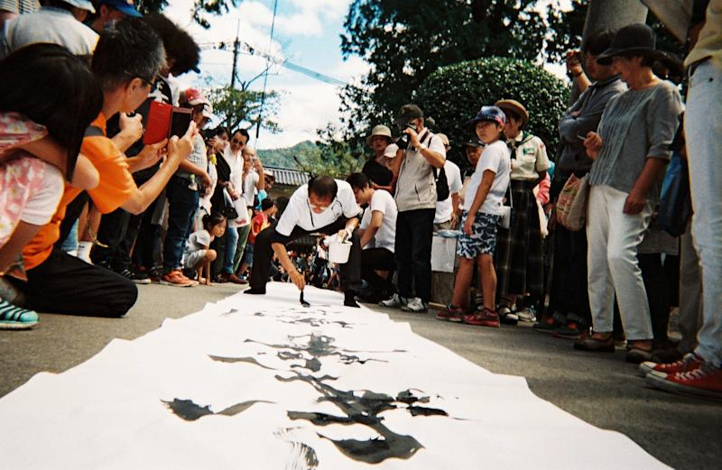 A fude-shi brush master writes words onto paper over 30 meters long.