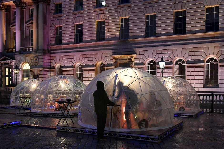 Staff deliver meals at a Winter Dome - outdoor dining pods erected for the month of December in the courtyard of Somerset House to enable restaurant eating, as English second lockdown restrictions were lifted amid the spread of the coronavirus disease (COVID-19), Britain, December 3, 2020. Picture taken December 3, 2020. REUTERS/Toby Melville