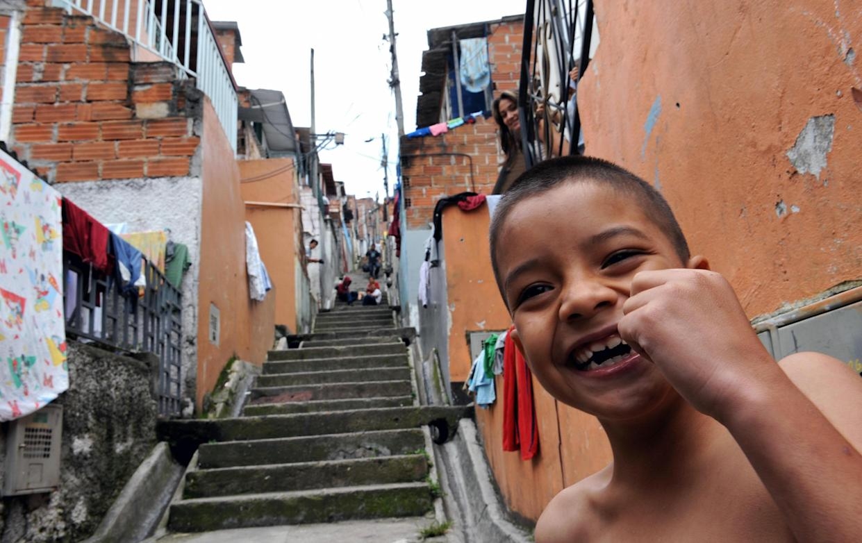 A boy smiles in the Pablo Escobar neighborhood -500 houses built by the Colombian drug lord for the poor- in Medellin, Antioquia department, Colombia on August 22, 2008. A tour operator created the