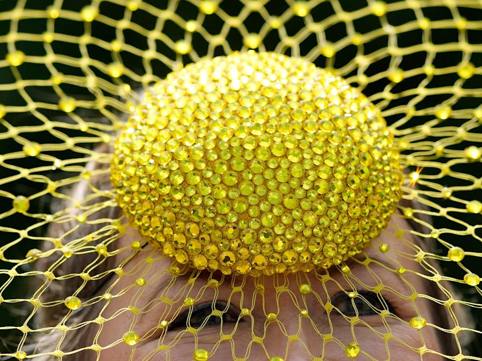 A close-up of a person wearing a yellow bedazzled hat with a mesh and glitter detail at the Royal Ascot racing event.