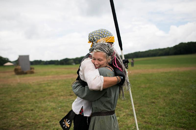 Attendees hug on the field while training for battle.  (Photo: Maddie McGarvey for HuffPost)