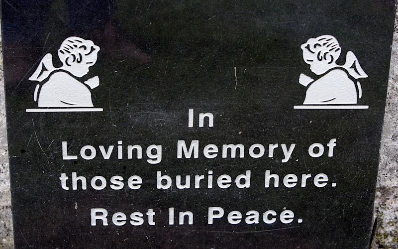 a plaque at shrine in Tuam, County Galway on June 9, 2014, erected in memory of up to 800 children who were allegedly buried at the site of the former home for unmarried mothers run by nuns - Credit: AFP