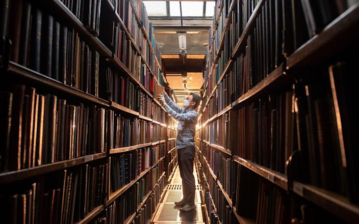 Chung Hoon arranges books in the rear book stacks at the London Library - Dominic Lipinski/PA Wire