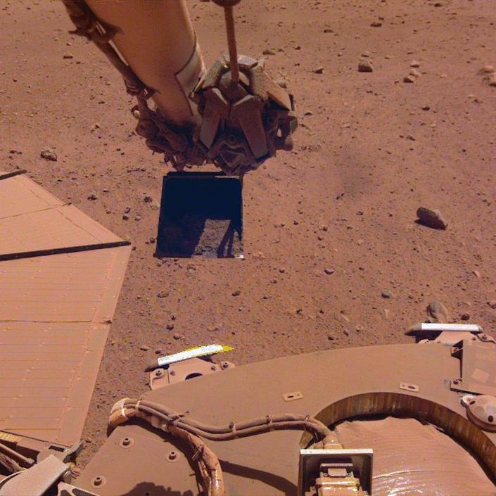 insight robotic arm scooping and trickling sand near solar panels gif