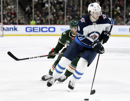 FILE - In this April 2, 2019, file photo, Winnipeg Jets defenseman Jacob Trouba (8) has the puck while shorthanded against Minnesota Wild center Luke Kunin (19) during the second period of an NHL hockey game in St. Paul, Minn. The New York Rangers have acquired Trouba from the Jets for defenseman Neal Pionk and the 20th overall pick in the draft. The teams announced the trade Monday, June 17, 2019. (AP Photo/Hannah Foslien, File)