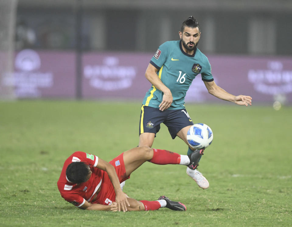Australia's Aziz Behich, top, and Nepal's Sunil Bal fight for the ball during the World Cup 2022 Group B qualifying soccer match between Nepal and Australia in Kuwait City, Kuwait, Friday. June 11, 2021. (AP Photo/Jaber Abdulkhaleg)