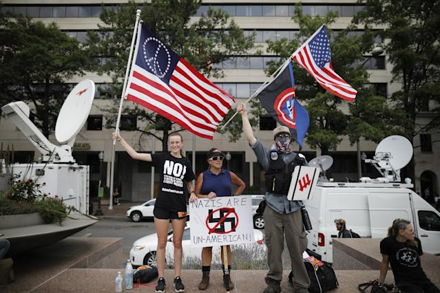 <p>Counter-protesters hold signs and flags ahead of the Unite the Right 2 rally in Washington, D.C., U.S., on Sunday, Aug. 12, 2018. The rally, being held in Lafayette Park near White House, marks the one-year anniversary of the Charlottesville, Virginia, rally where a car driven into a crowd of counter protesters killed 32-year-old Heather Heyer. (Photo: Aaron P. Bernstein/Bloomberg via Getty Images) </p>