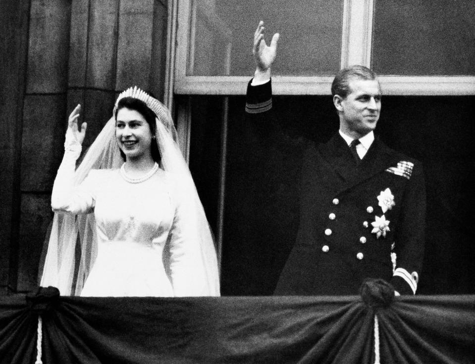 FILE - In this Nov. 20, 1947 file photo, Britain's Princess Elizabeth and her husband the Duke of Edinburgh wave to the crowds on their wedding day, from the balcony of Buckingham Palace in London. In 1947. Philip married Britain's Princess Elizabeth, the elder daughter of King George VI, and when she became queen at the age of 25 in 1952, Philip gave up his naval career and dedicated himself to supporting her and the monarchy. Prince Philip who died Friday April 9, 2021, aged 99, lived through a tumultuous century of war and upheavals. (AP Photo/File)
