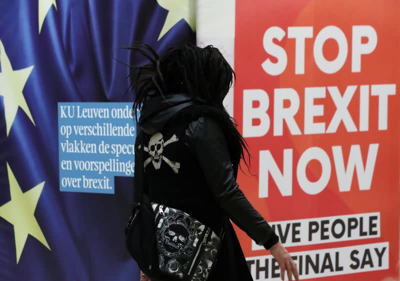 "A woman walks past a billboard depicting a photo of a placard reading ""Stop Brexit Now"" at Central railway station in Brussels"