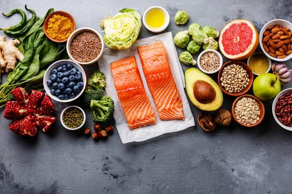 A spread of healthy foods including salmon, avacado, blueberries.