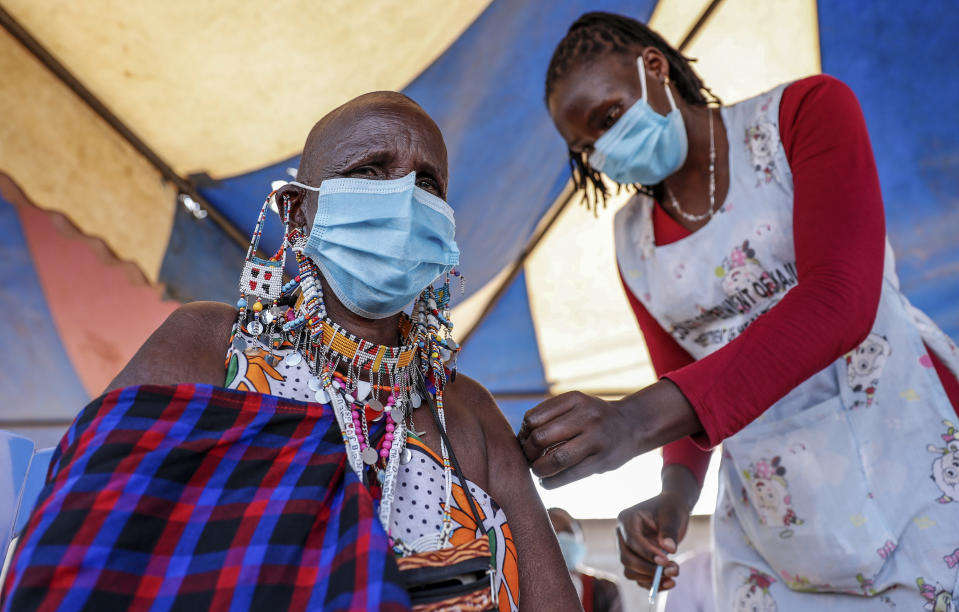 A Maasai woman receives the AstraZeneca coronavirus vaccine at a clinic in Kimana, southern Kenya Saturday, Aug. 28, 2021. Wealthier nations are awash in vaccines, while they are scarce in poorer countries and many people are still waiting for their first shot. (AP Photo/Brian Inganga)